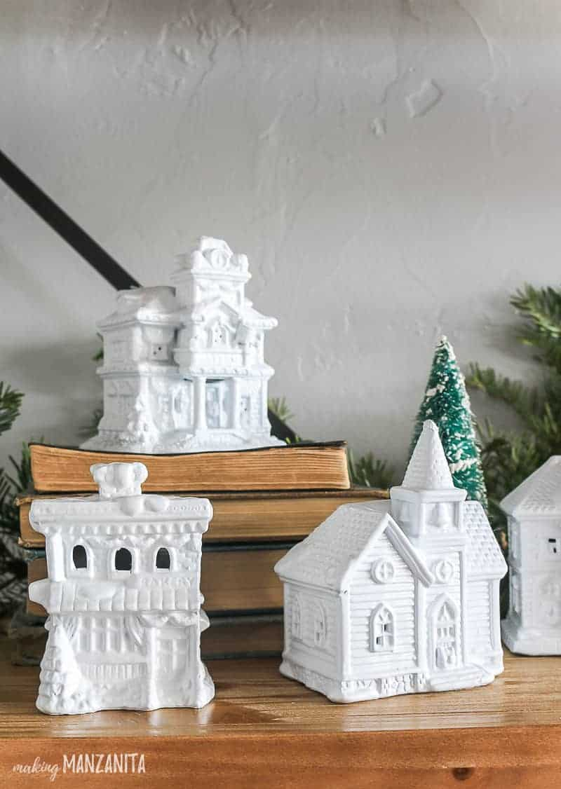 Christmas Village figurines display beside a mini Christmas tree and one on top of the books