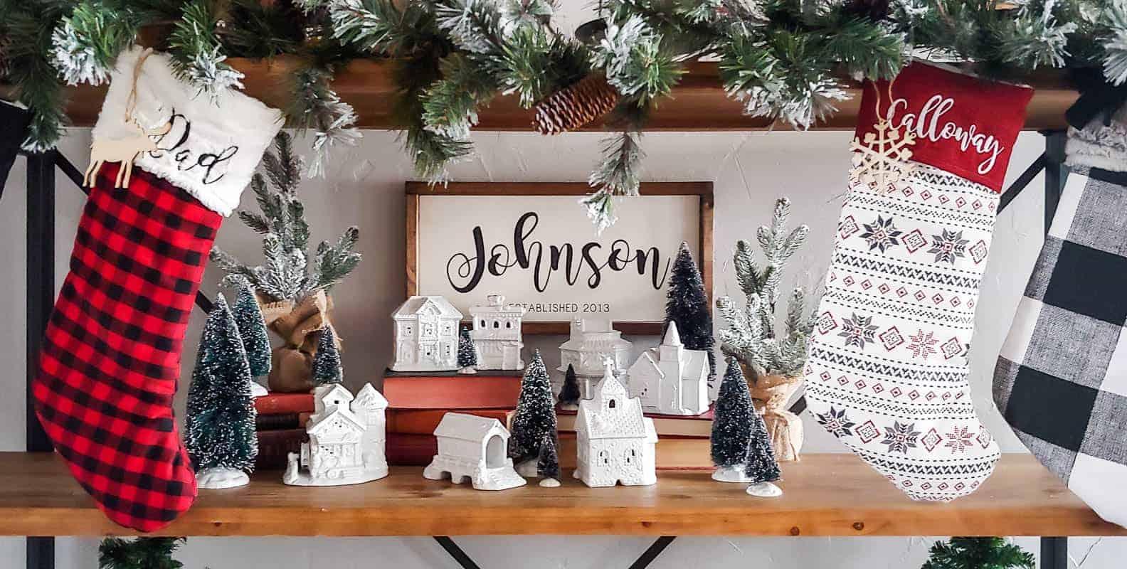 A mini Christmas village displayed on a Christmas themed shelf