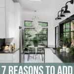 "Modern White kitchen with white cabinets, floors and walls with black accents and counter tops and a skylight. Text Overlay Says ""7 Reasons to Add Skylight"""