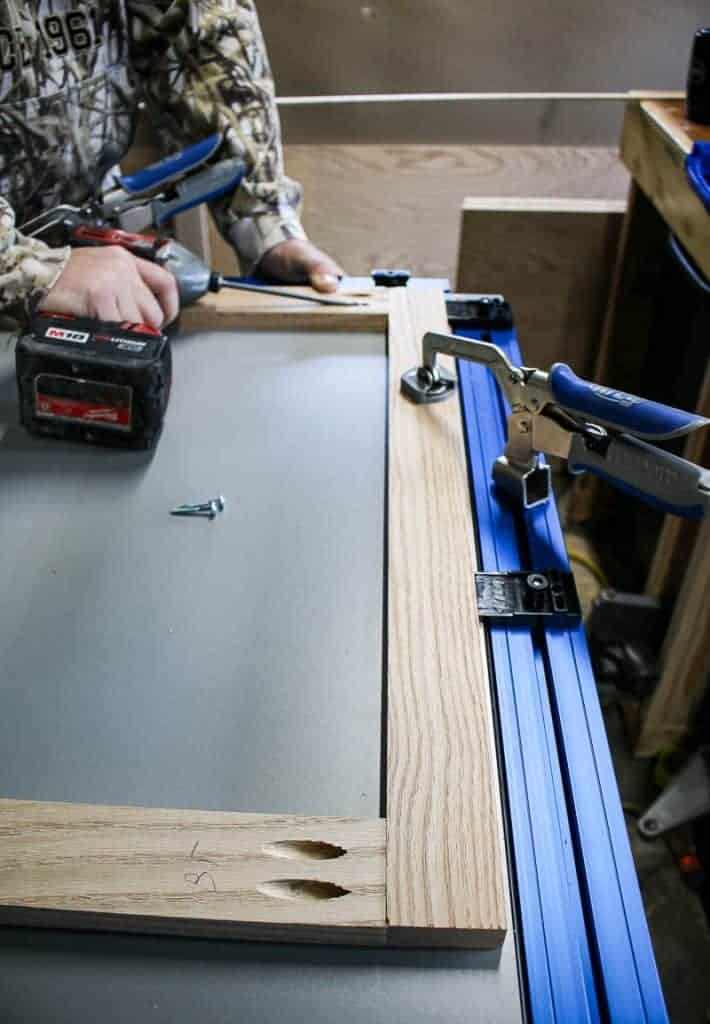 A clamp table is holding together a wooden face frame while a man is drilling in pocket hole screws