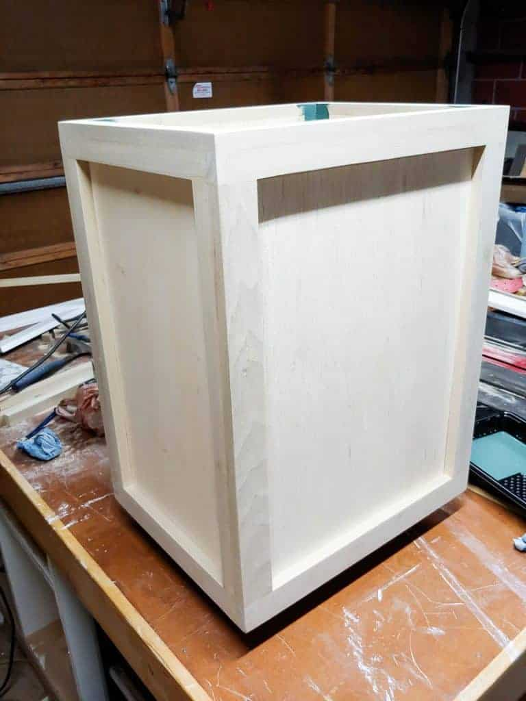 Shows a wooden laundry hamper in the process of being built on a workshop table
