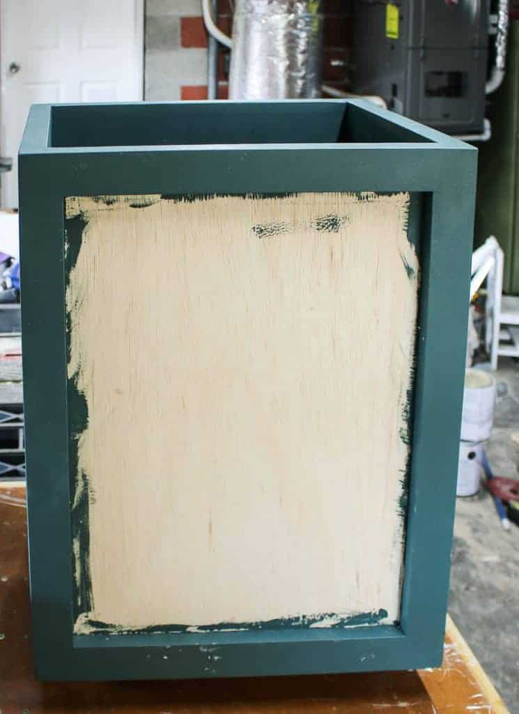 A wooden laundry hamper in process in in the middle of a project with painted teal edges