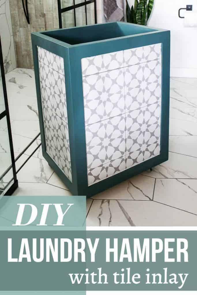 laundry hamper with teal trim and gray and white tile sitting in a white bathroom with tile flooring and white walls. That says DIY laundry hamper with tile inlay