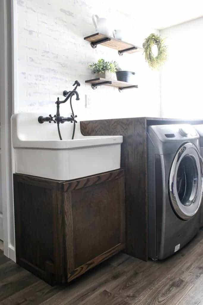 Farmhouse Laundry room with large farmhouse sink sitting on top of a wood cabinet and wood counter covering a washer and dryer with wood floors and while brick like walls and wood shelves