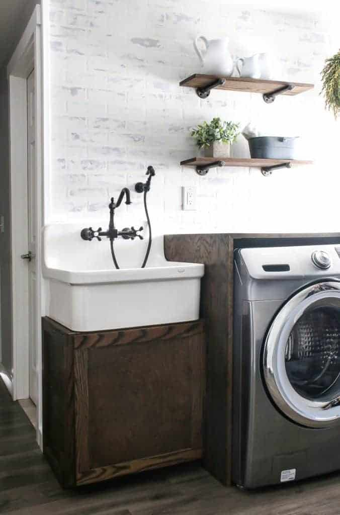 Modern looking farmhouse style laundry room with large farmhouse sink and vintage faucet and sprayer on top of a wood cabinet next to a wood counter top over a washer with white brick walls and wood floors