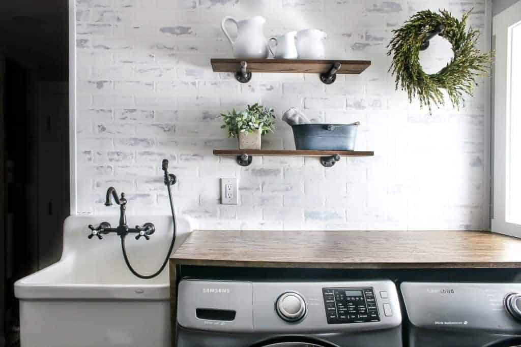 Farmhouse inspired laundry room with industrial-style shelving, a folding table over the washer and dry, and farmhouse sink