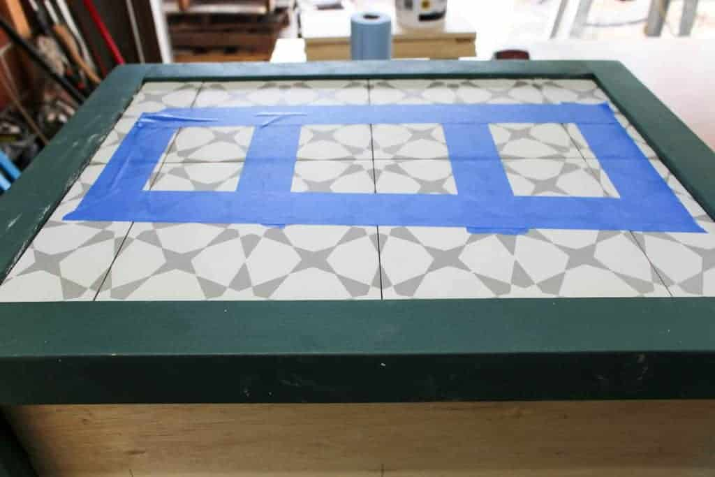 Side of a box with teal trim and white and gray tile inlay held on with blue painter's tape