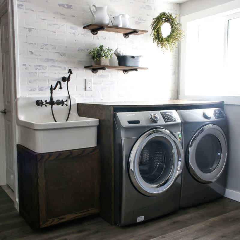 Farmhouse laundry room with farmhouse sink and wood counter over washer and dryer with wood floors and white brick walls