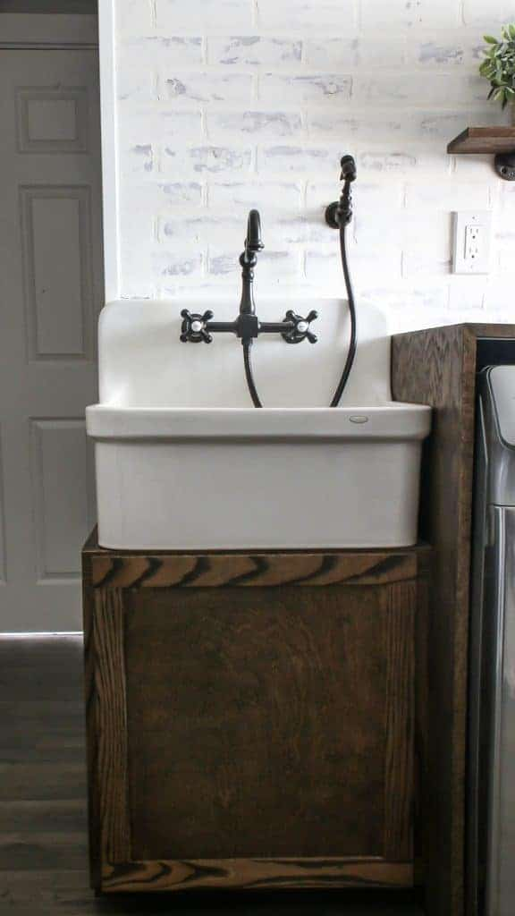Large farmhouse sink with vintage looking faucets and sprayer with wood cabinet and white washed faux brick walls