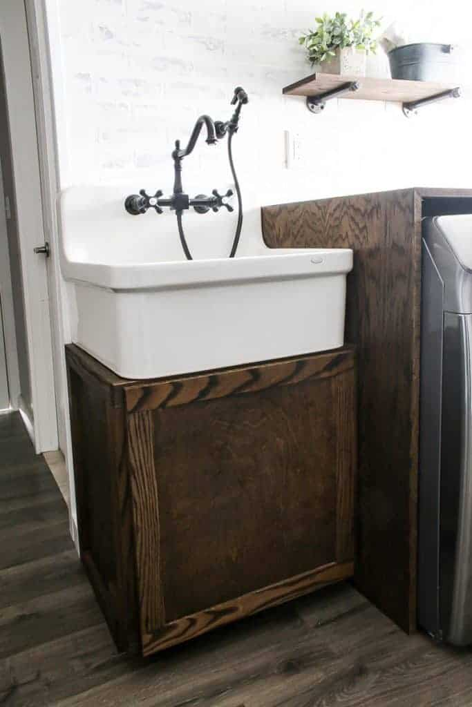 Farmhouse laundry room with large farmhouse sink and vintage faucet and sprayer on top of a wood cabinet with white brink walls and wood floors.