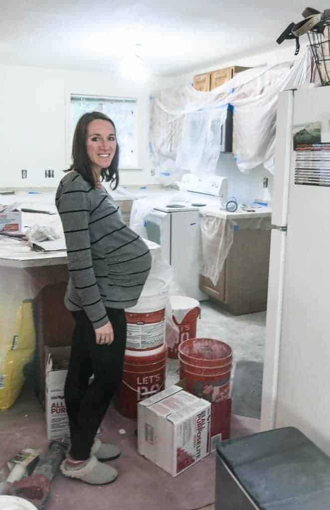 Woman standing sideways showing very pregnant belly standing in the middle of a renovation zone in the kitchen