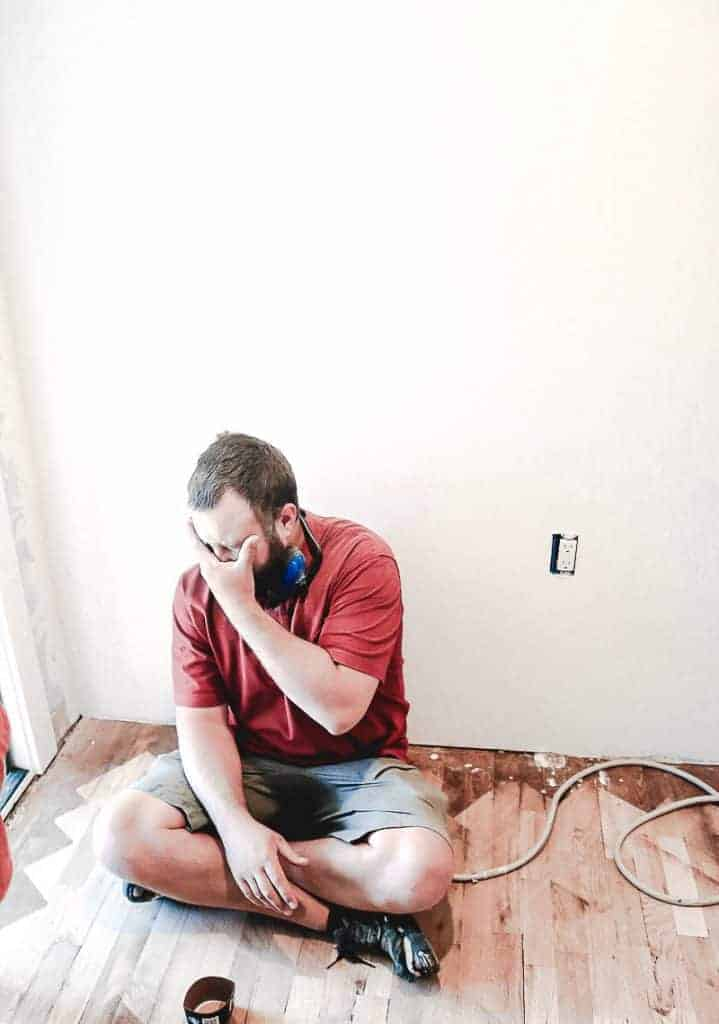 A man on the floor looking tired during a house renovation with wood floors and white walls
