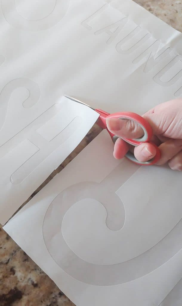 A pair of scissors are cutting out some letters from white contact paper