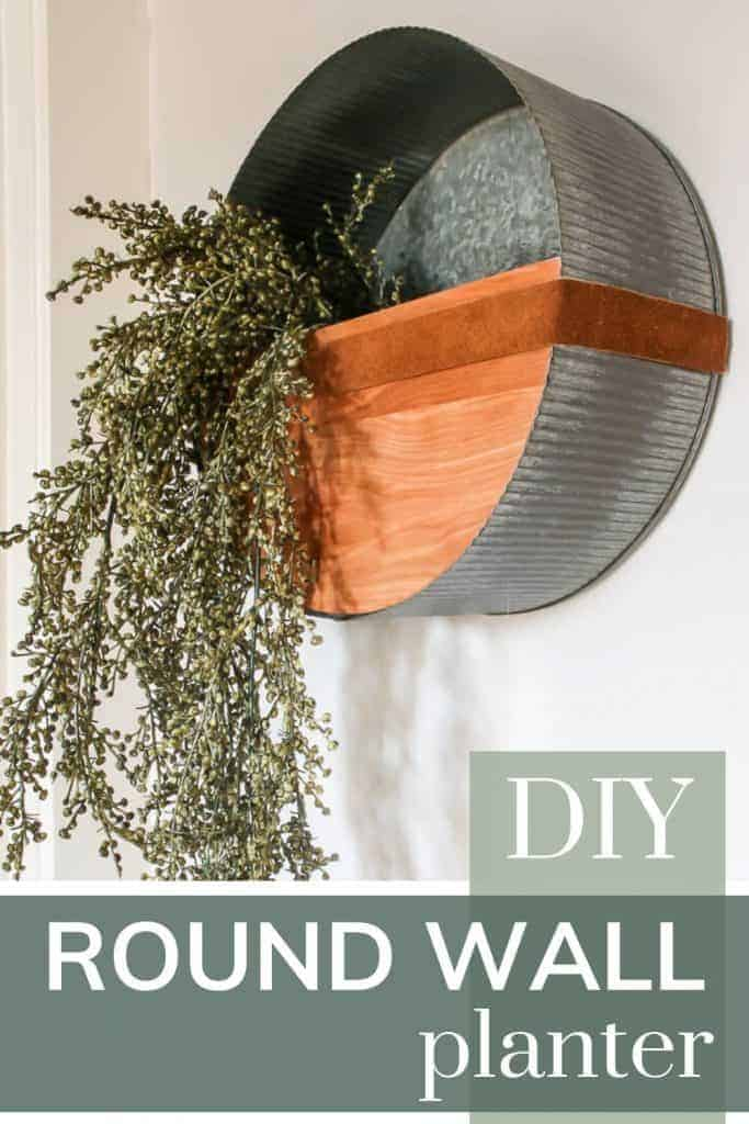 Side view of the modern metal wall planter on a white wall and long green vines hanging from it with text overlay that says DIY round wall planter