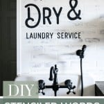 A face on view in a modern farmhouse laundry room with white walls and farmhouse sink with writing above on the walls that says wash and dry laundry service and says at the bottom with text overlay DIY Stenciled Words On Wall