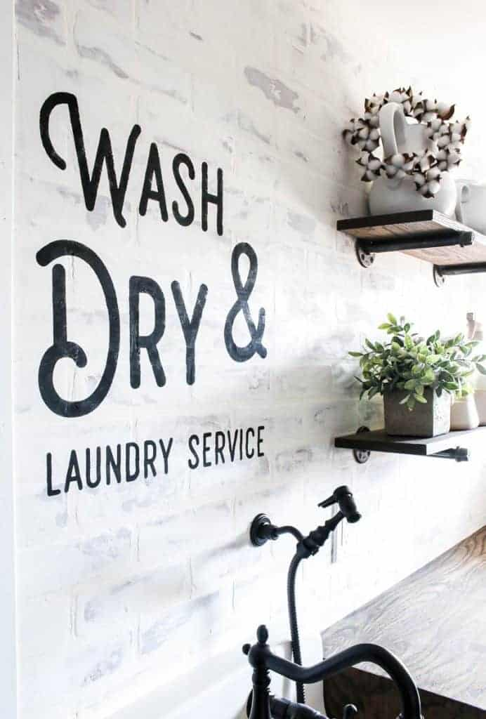 A view of the white faux brick wall and farmhouse shelves with black writing from the wall stencil that says wash and dry laundry service