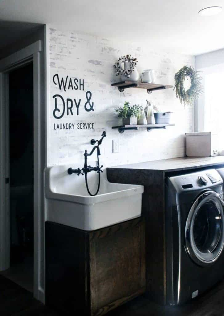 Farmhouse laundry room with white walls and farmhouse sink with writing on the walls that says wash and dry laundry service above farmhouse sink