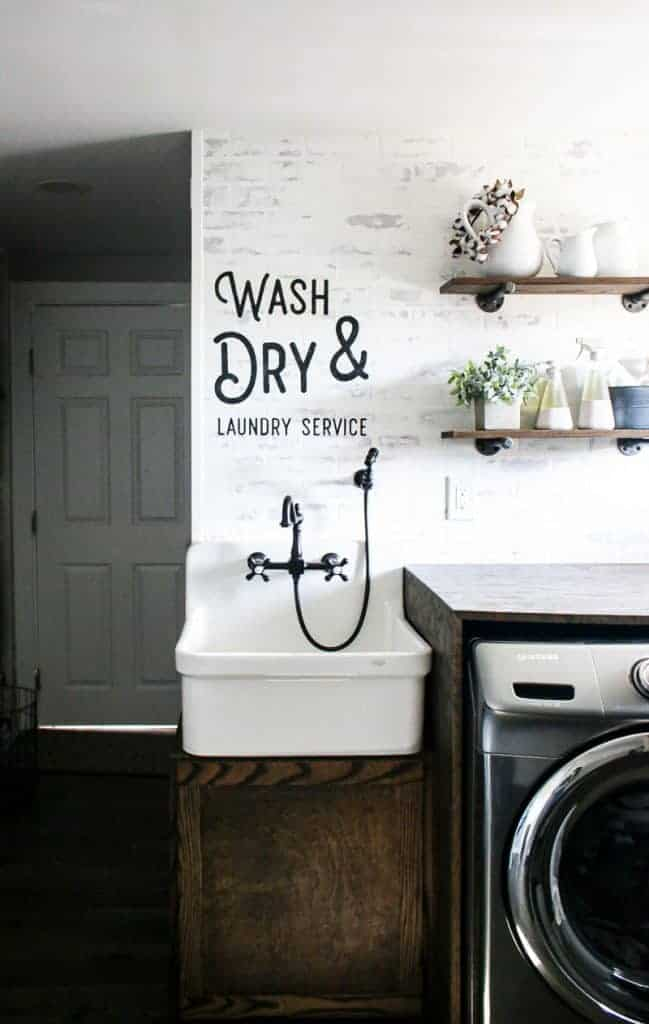 A face on view in a modern farmhouse laundry room with white walls and farmhouse sink with writing above on the walls that says wash and dry laundry service