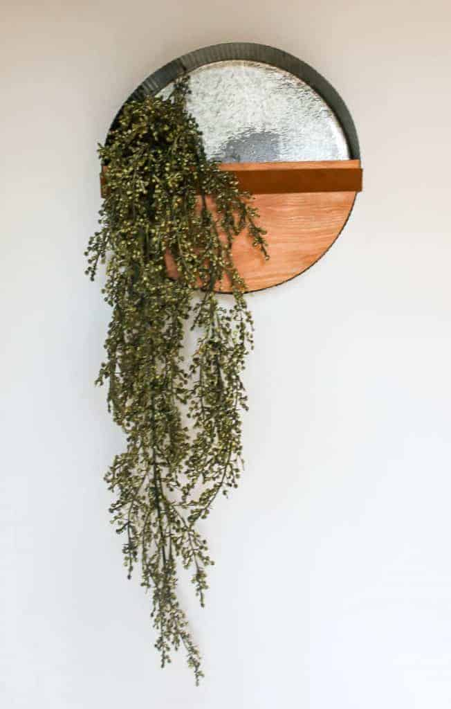 metal wall planter with green vines and wood bottom on a white wall
