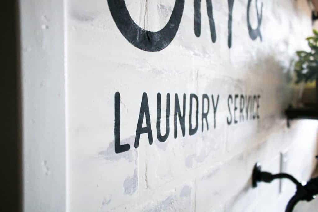 side view of the white walls with black writing that says laundry service