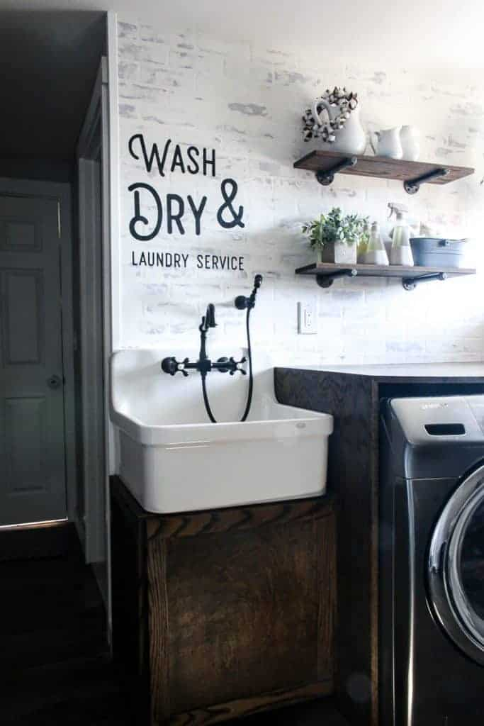 Farmhouse laundry room showing faux brick wall, white farmhouse sink with black faucet, folding counter over washing machine, industrial floating shelves and stenciled quote on the wall above sink