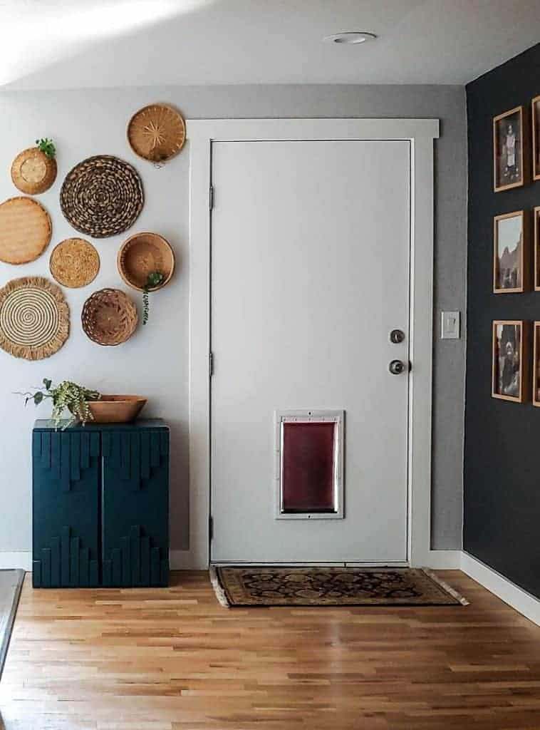Shows a boho entry way with wicker baskets hanging on a white wall with a white door, wood floors, and green boho cabinet