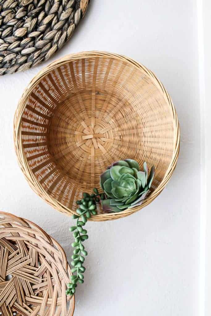 shows up close photo of wicker baskets with a succulent on a white wall