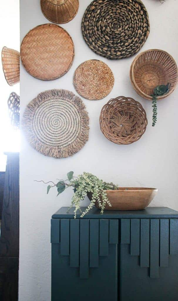 shows a close up photo of the various types of wicker baskets on a white wall with a green cabinet below