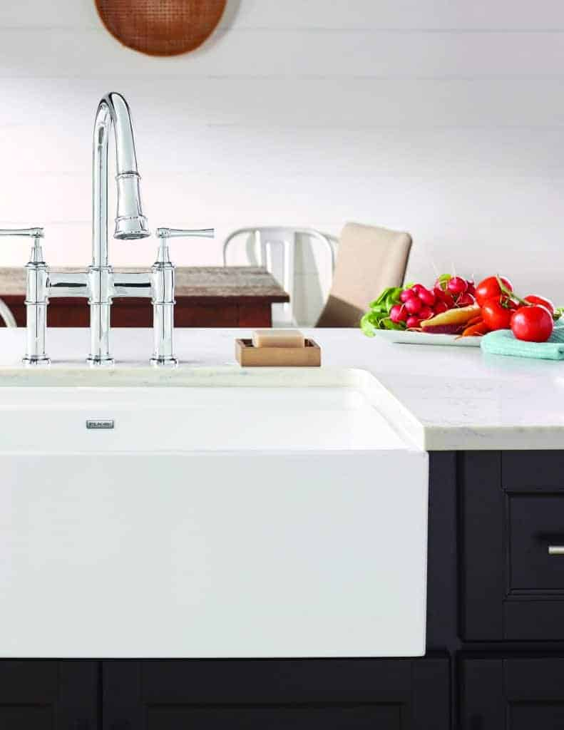 Shows a white fireclay farmhouse sink with stainless steel faucet in modern kitchen with fresh veggies on countertop