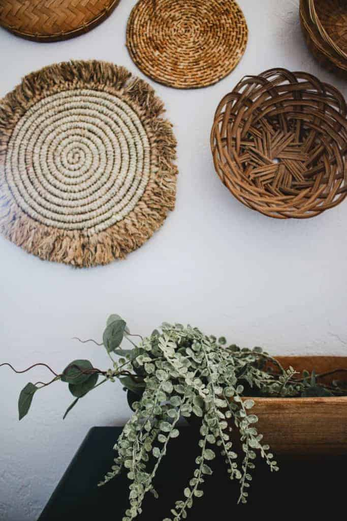 shows different types of wicker baskets on a white wall with a wooden bowl of greenery sitting on a cabinet