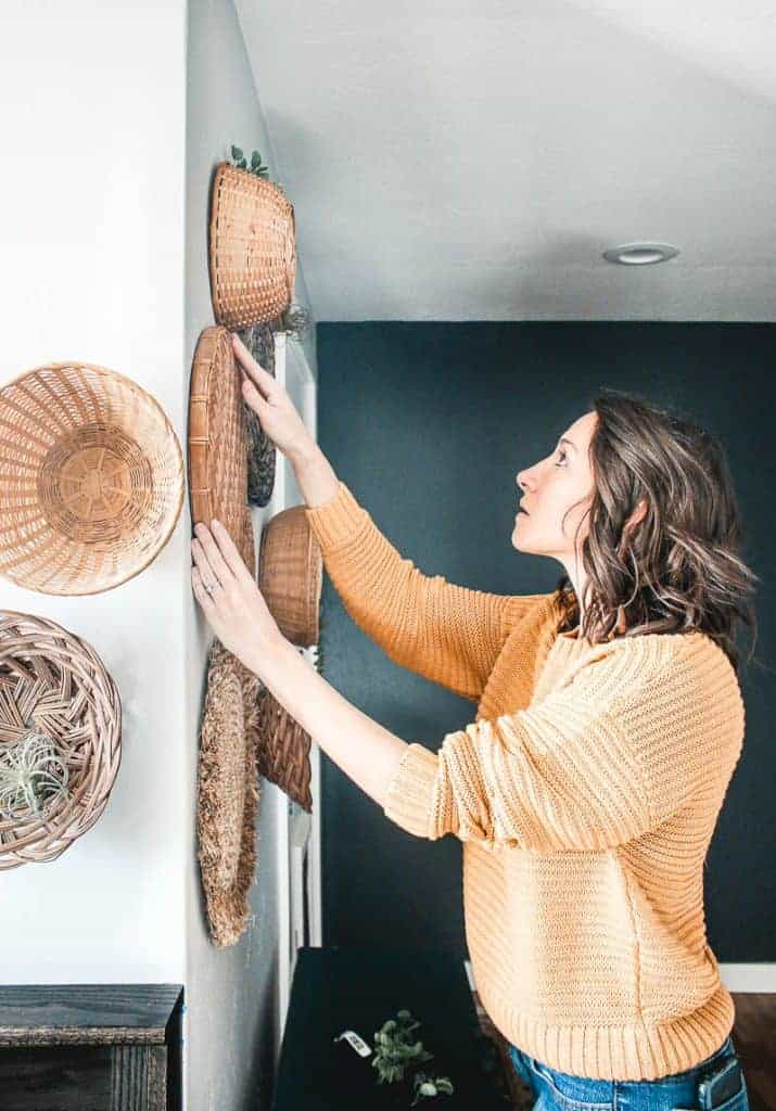 A woman is placing a wicker basket on her walls with various other baskets