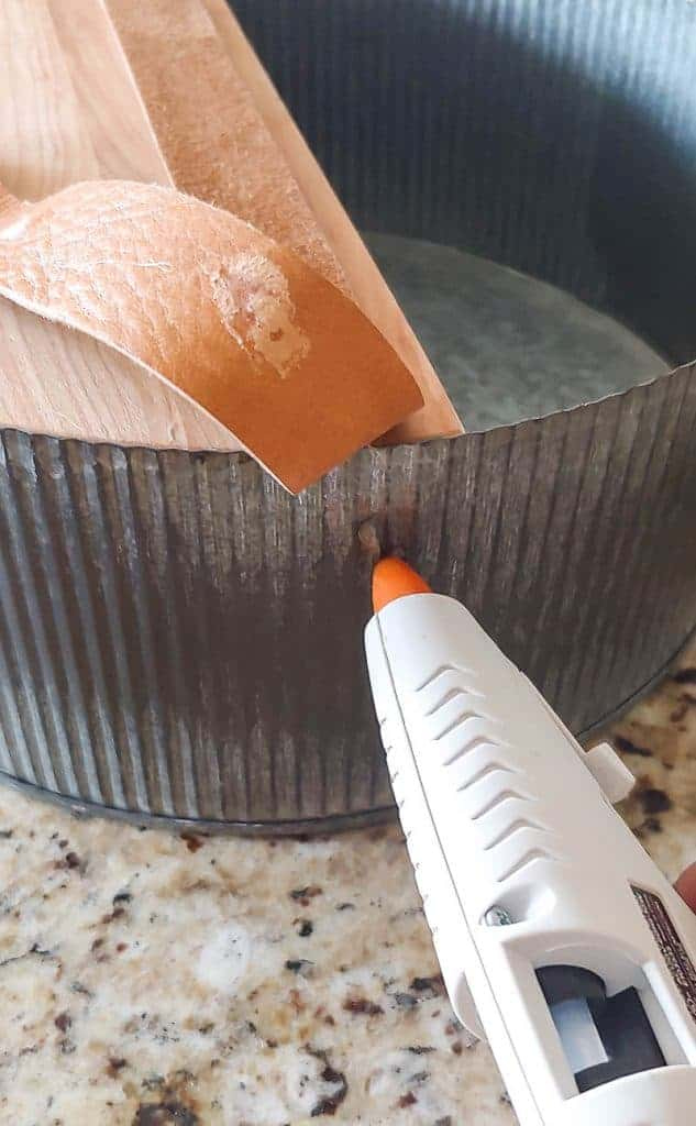 A hot glue gun is gluing a piece of leather to the side of a galvanized basket with a piece of wood at the bottom