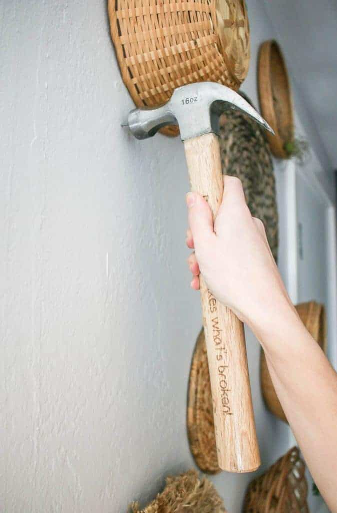 Shows a hammer nailing in a nail into a white wall with various other wicker baskets hung in the background