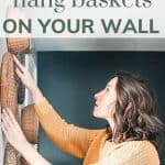 A woman is placing a wicker basket on her walls with various other baskets with text overlay that says learn how to hang baskets on you wall