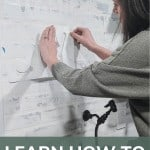 A person pinning the stencils to a white faux brick wall over a sink. On bottom it says learn how to stencil on the wall