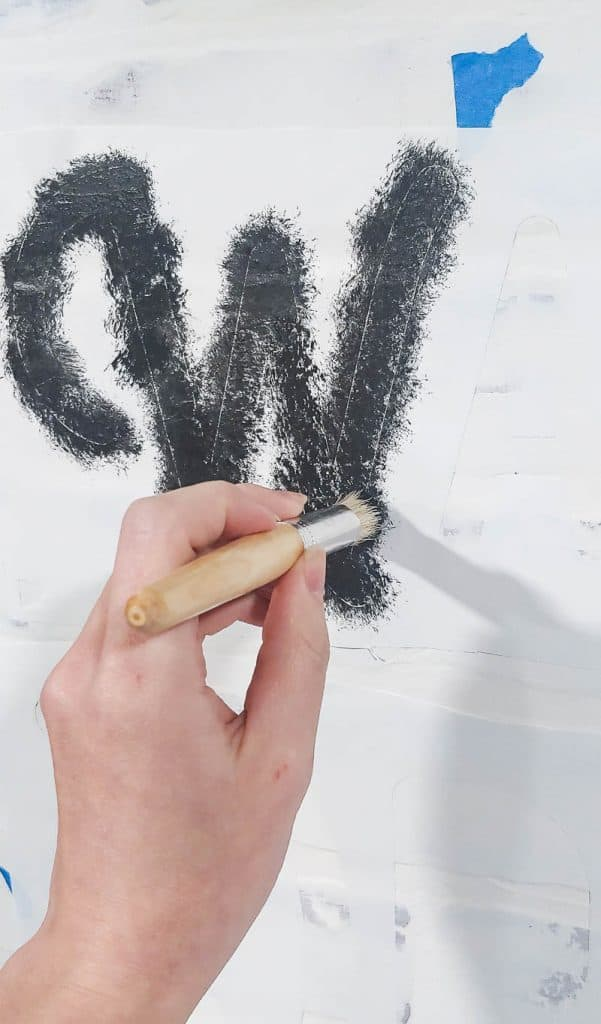 The W from a wall stencil is being painted black onto a white wall