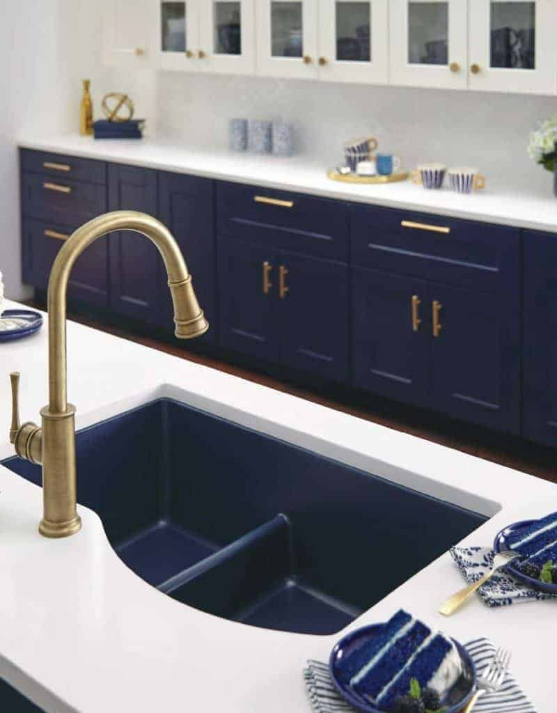 shows a modern blue and white kitchen with metal faucet.