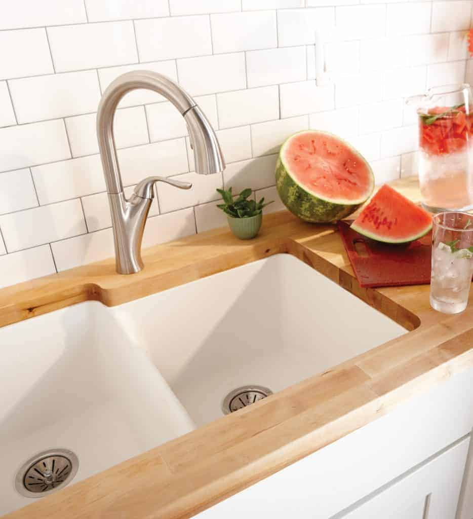 shows a modern white quartz sink with white tile backsplash and wood counter top and has metal faucet and watermelon next to it