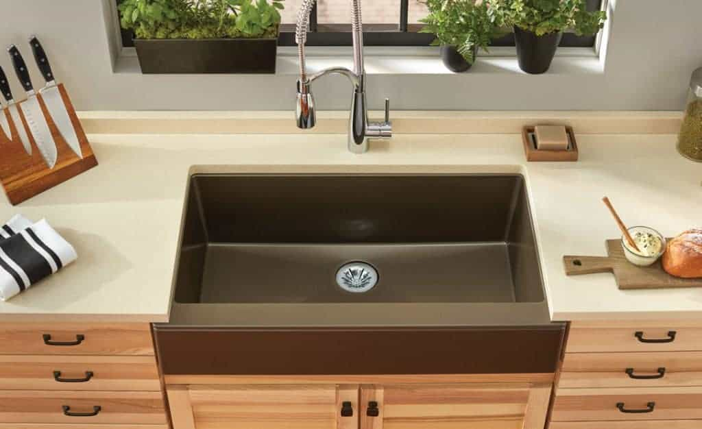 shows a modern kitchen with wood cabinets and brown apron sink with a metal faucet and gray walls