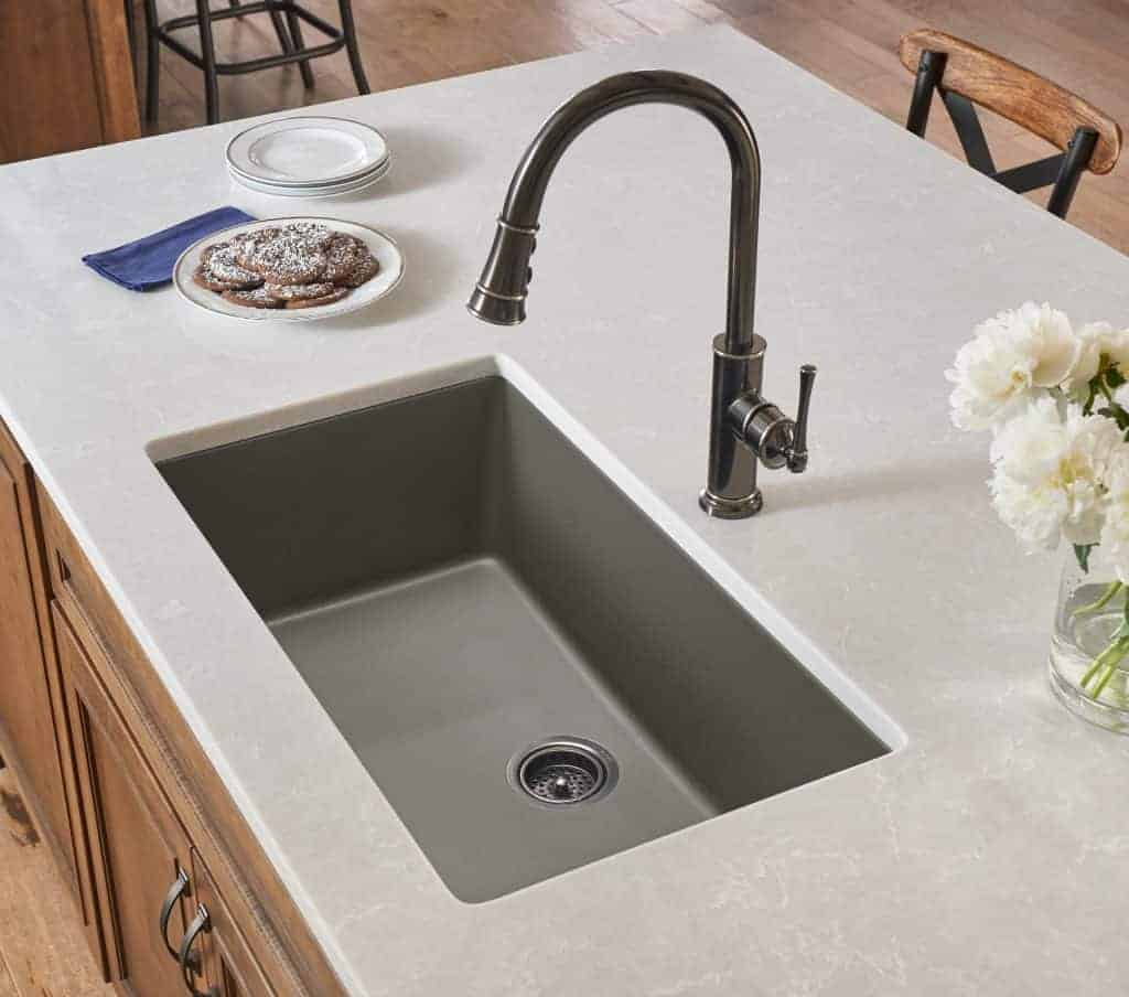 shows a modern kitchen with marble counter top and gray sink with a metal faucet and wood cabinets