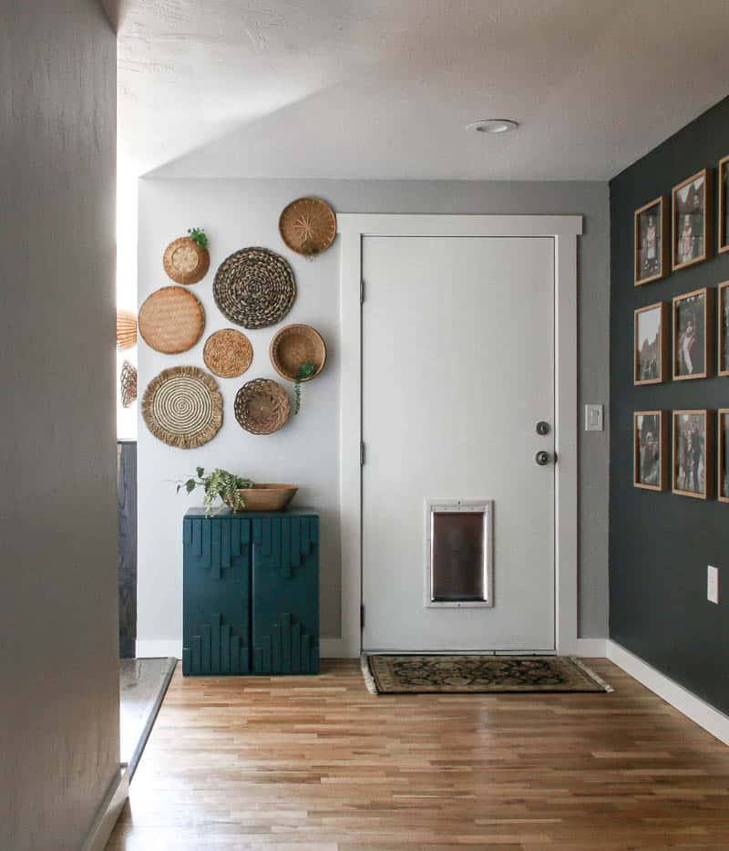 Shows a boho entry way with wicker baskets hanging on a white wall with a white door, wood floors, and teal cabinet. And a gray wall on the other side