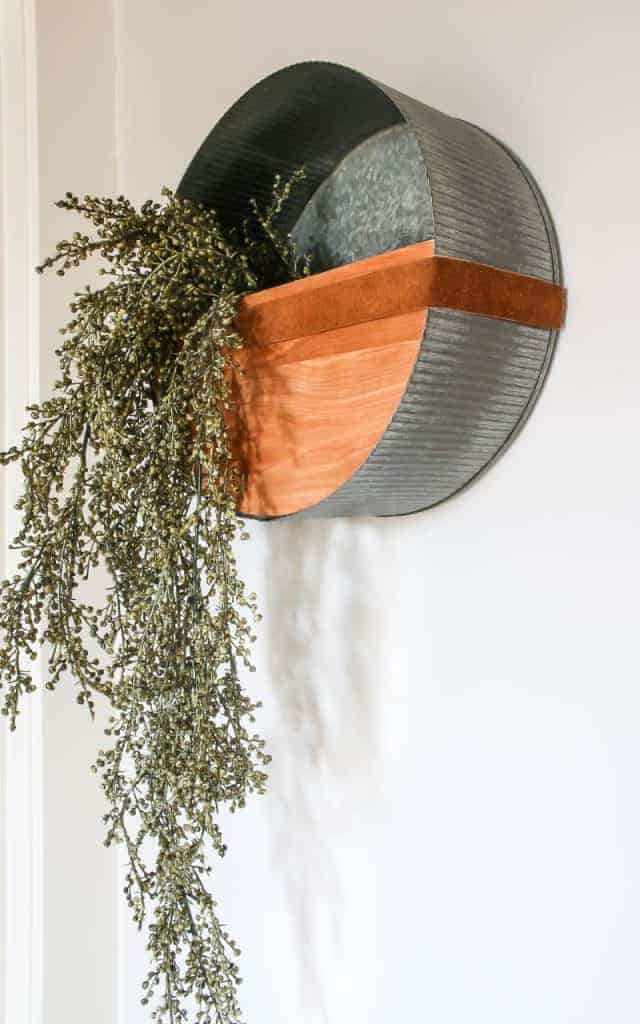 Metal basket on a white wall with wood and leather that is holding some greenery