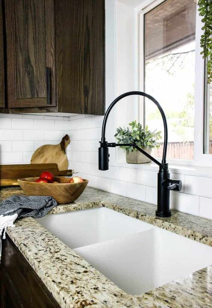 shows a farmhouse kitchen with a black faucet, granite counter top, and white subway tile backsplash.