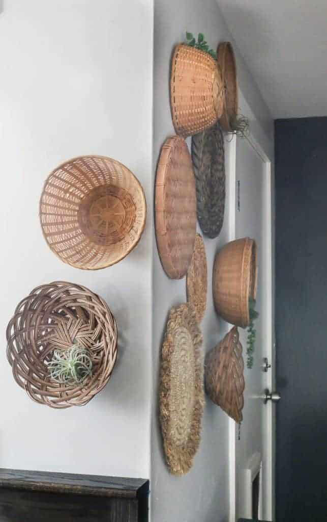 shows a side angle of various types of wicker baskets on a white wall that wrap around the corner