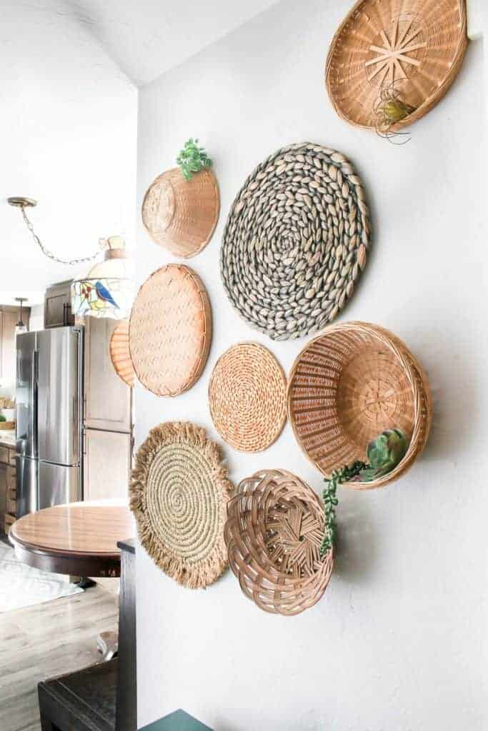 Shows an upward angle of the various wicker baskets on a wall with tiny succulents in the baskets with a kitchen in the background