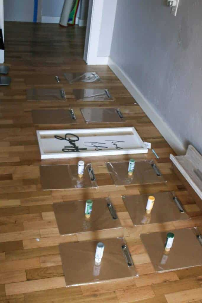 Shows a layout of 12 clipboards on the wood floors with various paint tubes sitting on top of them in front of a gray wall
