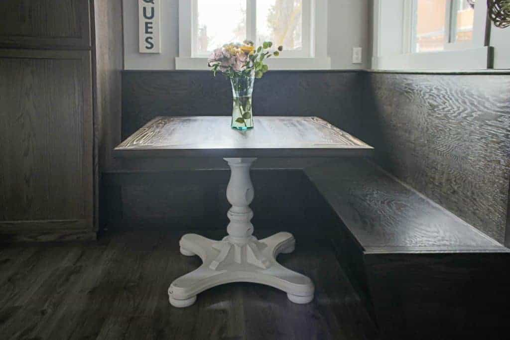 shows a dark wood farmhouse nook with a wood table with a painted white bottom stand