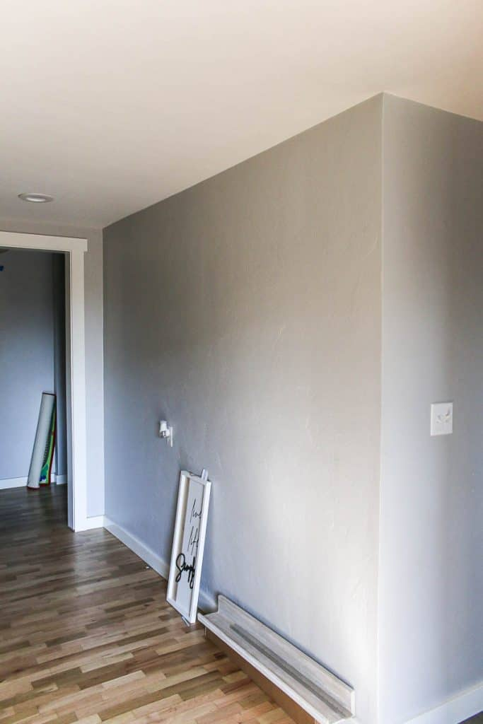 Shows a blank gray wall with a frame on the wood floors