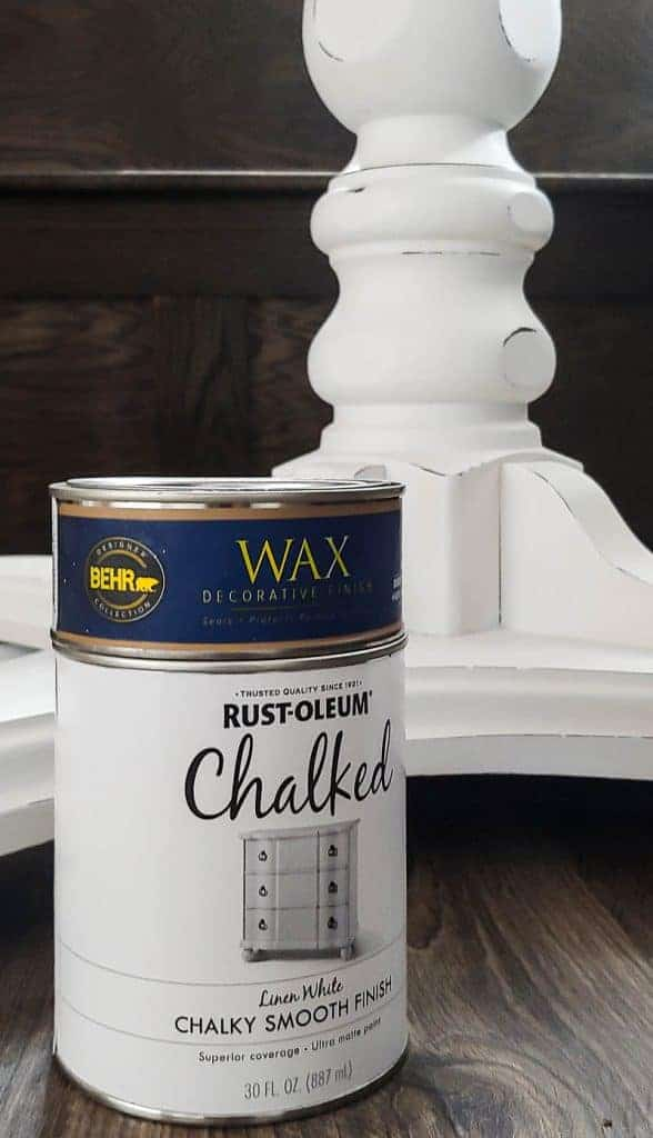 shows the white stand of a table with a can of Rust-Oleum chalked paint and a can of Behr wax finish on a wood floor