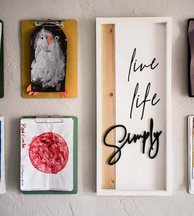 shows clipboards with kids artwork hanging from them on a gray wall next to a white live life simply frame